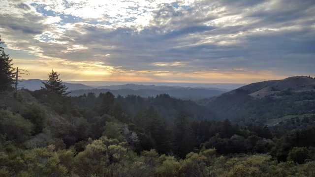 Photo of the sun setting over the Pacific Ocean across the foothills of the Santa Cruz Mountains